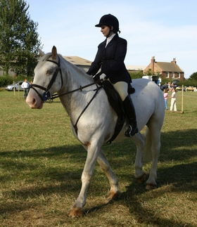 Girl fully dressed smartly riding a white horse in a field