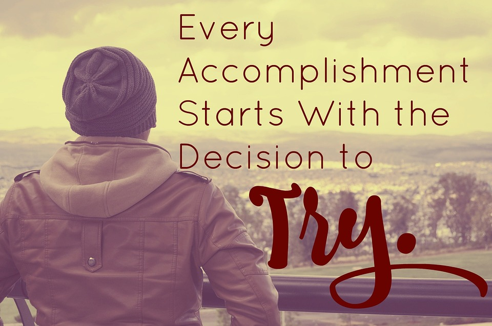 'every accomplishment starts with the decision to try' written over a person looking over landscape