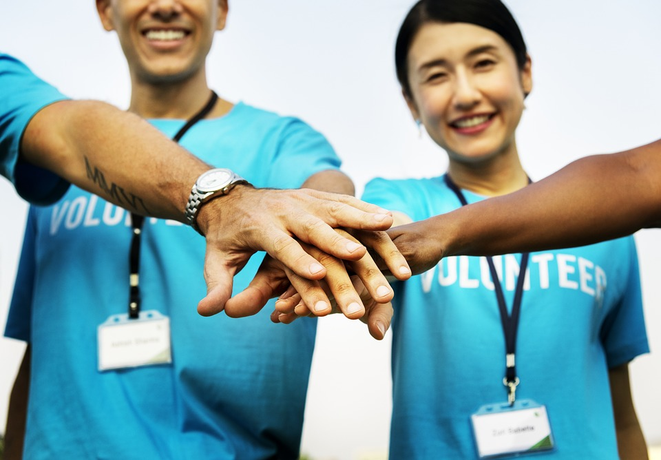 volunteers putting hands together in the centre and smiling