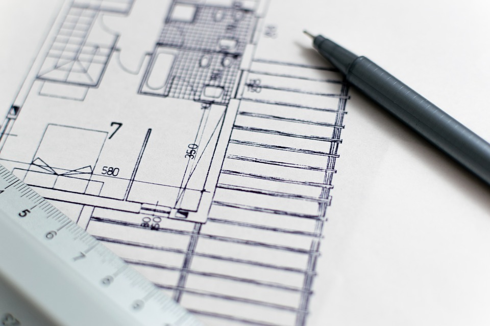 a drafting pencil sits onn top of complicated architectural drawings