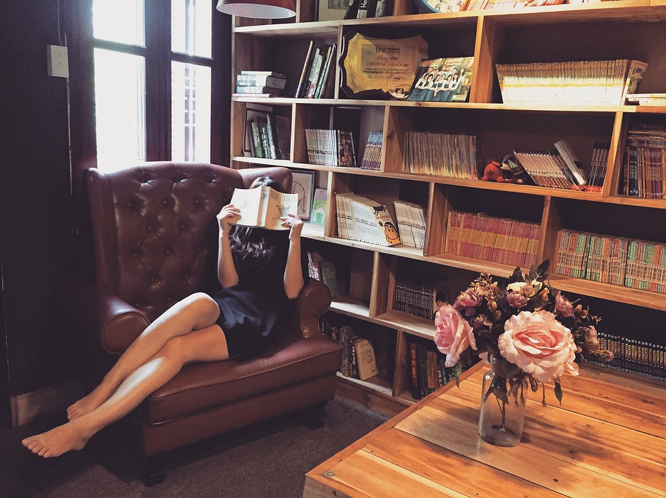 woman reading in a library with pink roses on a table nearby