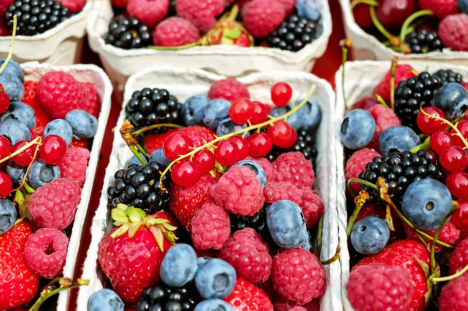 Different fruits and berries in cardboard baskets