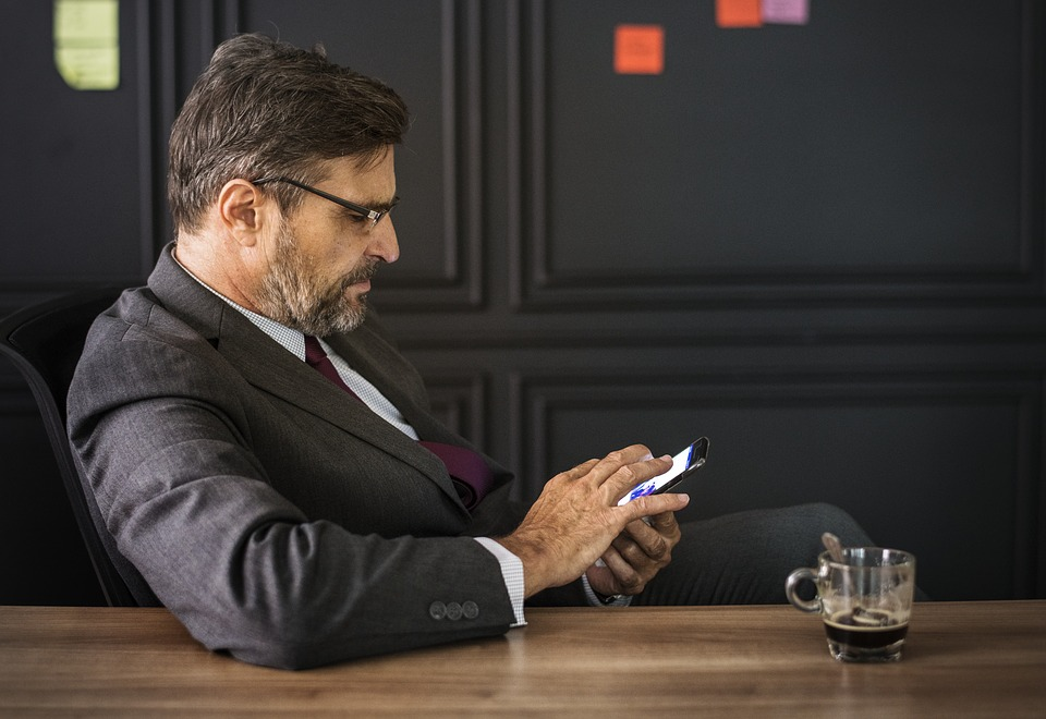 a man is in an office on the phone with a coffee beside him