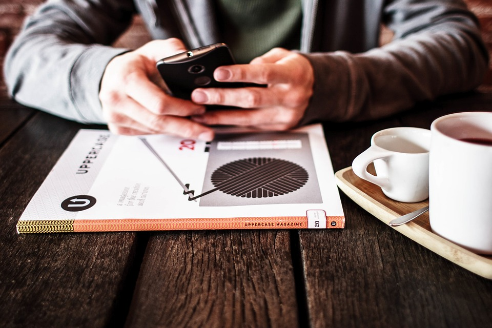 person sitting with a mobile phone in their hands with coffee next to them over a textbook