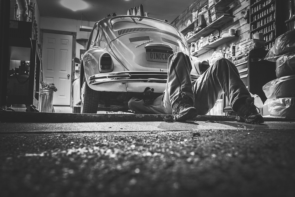 man under a vintage car repairing it. Black and White