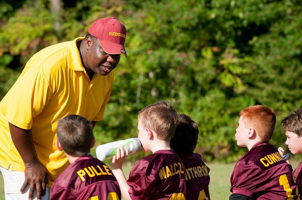 man in yellow shirt coaching children for football on a green field