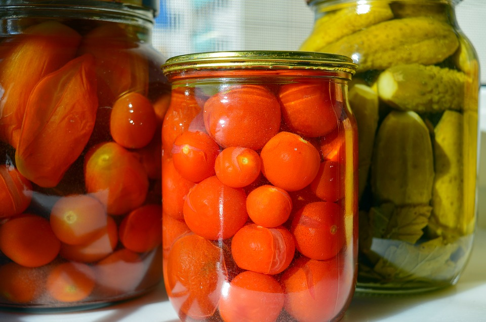 3 jars of preserved vegatbles. At the front is a jar of pickled tomatoes. On the left, a jar of plum tomatoes and to the right, a jar of pickles