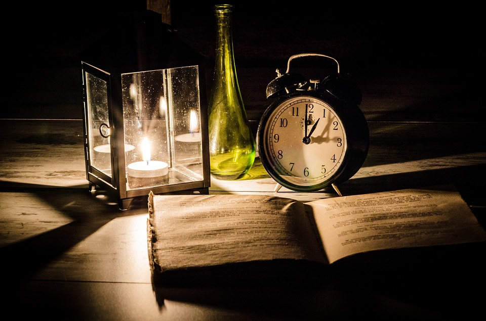 candle lamp, green bottle, alarm clock and old book open on a desk