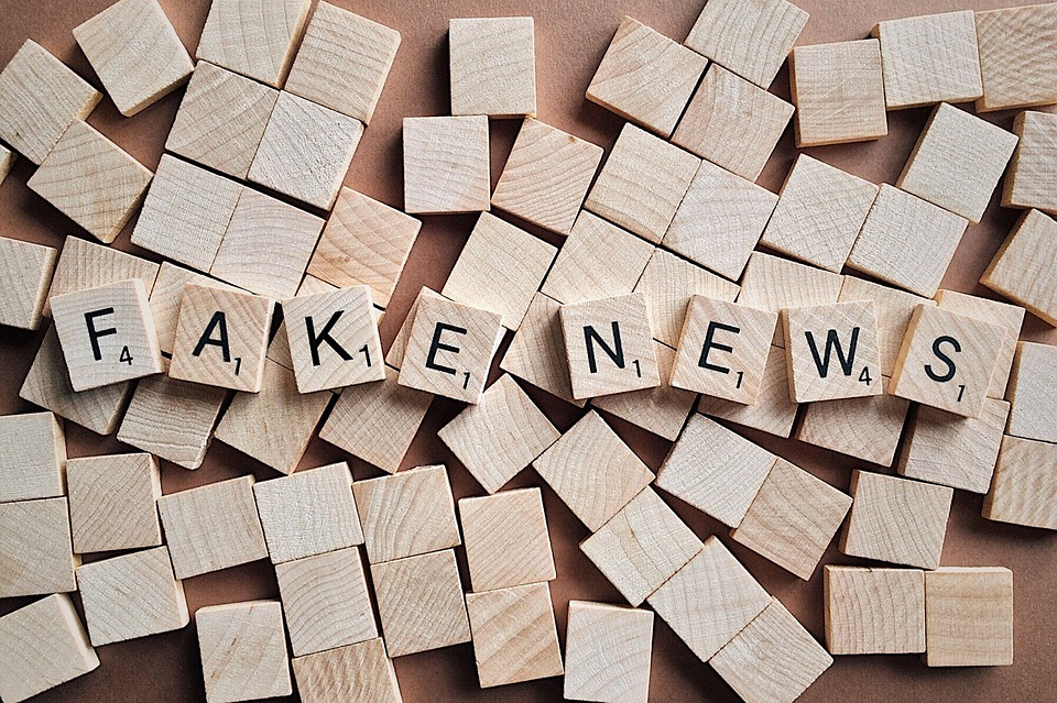 fake news in spelled out in scrabble tiles over blank tiles