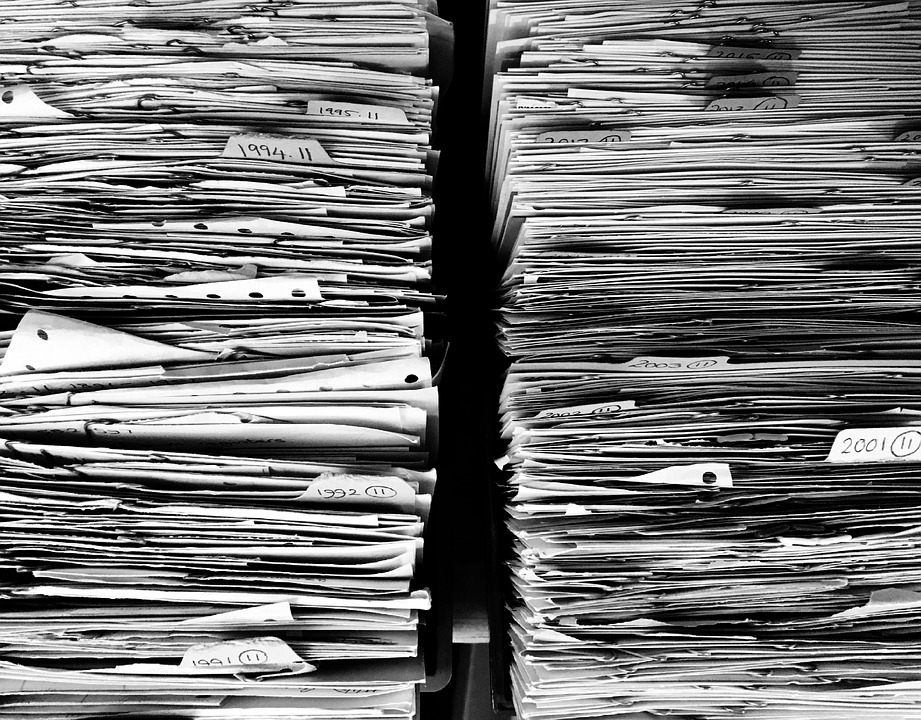 two massive stacks of paper fill the entire frame, representing unfinished paperwork