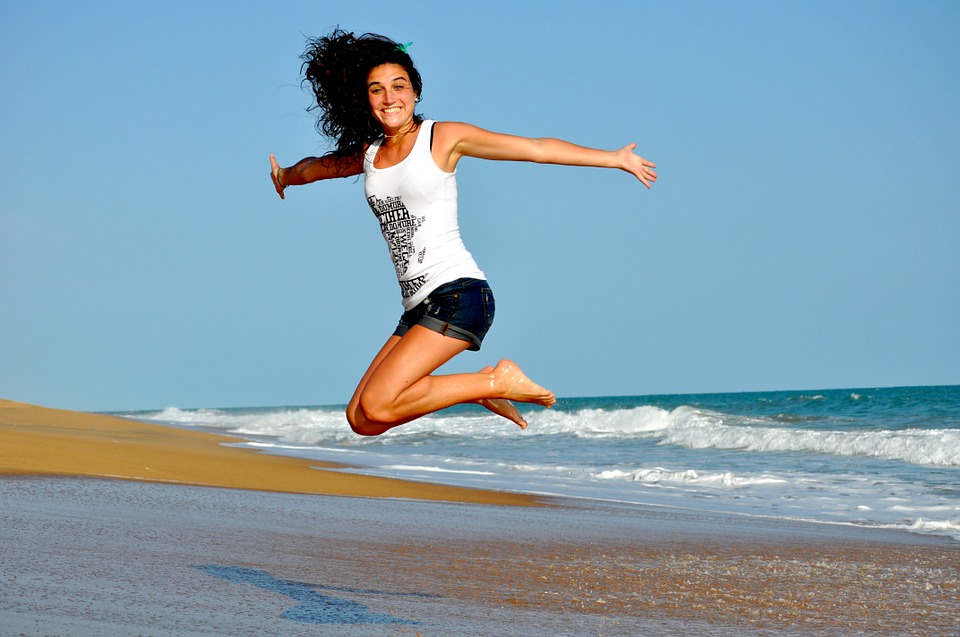 woman jumping with arms wide open