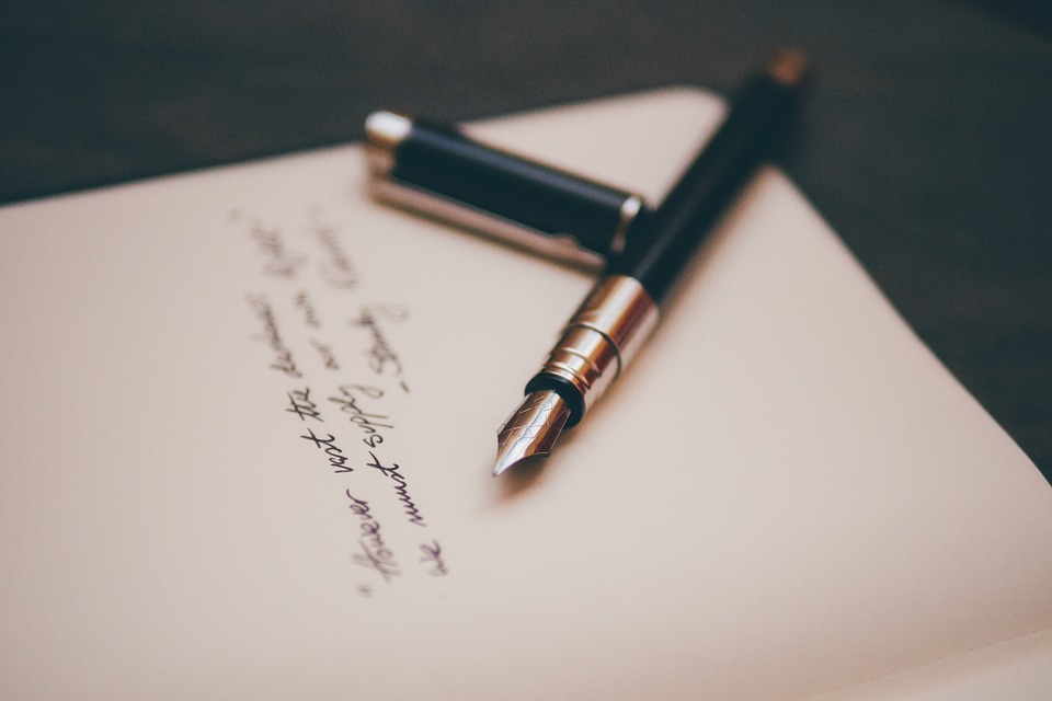 Beautiful fountain pen and cursive over white paper