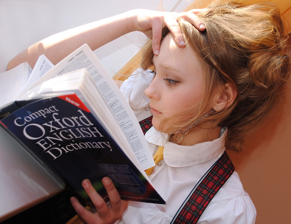 girl reading through the oxford english dictionary