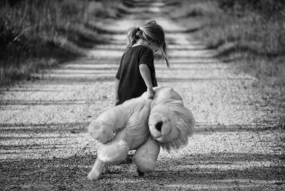 girl with teddy walking along a path
