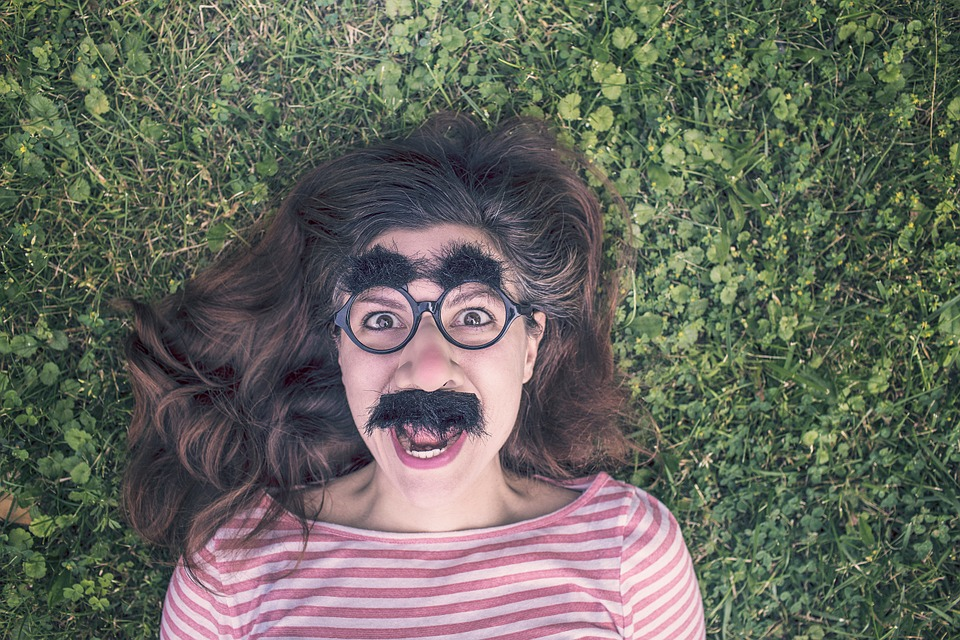 woman lying on grass with silly glasses, moustache and eyebrows on, smiling