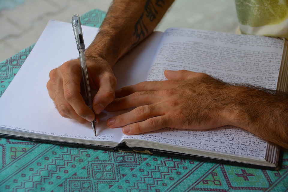 hands writing in a journal