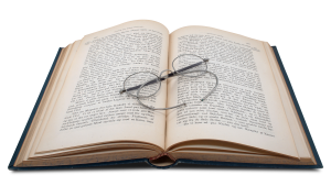 book open with glasses lying across the page