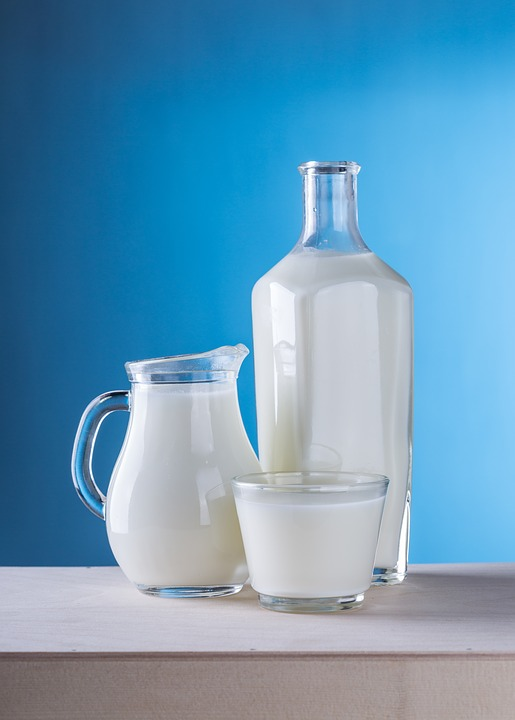 A glass, a jug and a bottle are all filled with milk