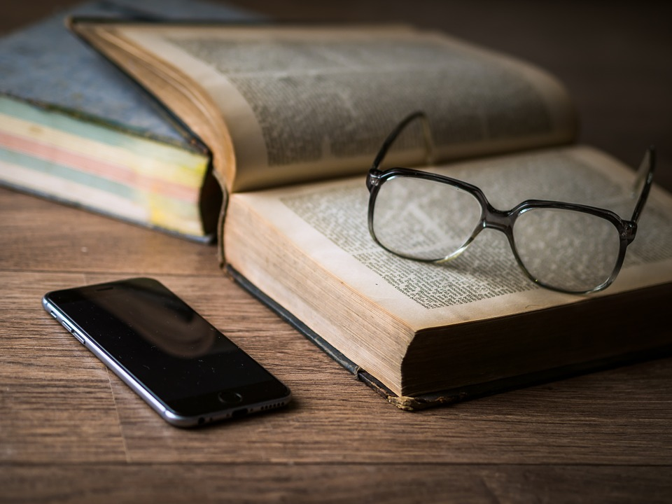 A phone rests on a table beside an old book which has a pair of glasses on it.