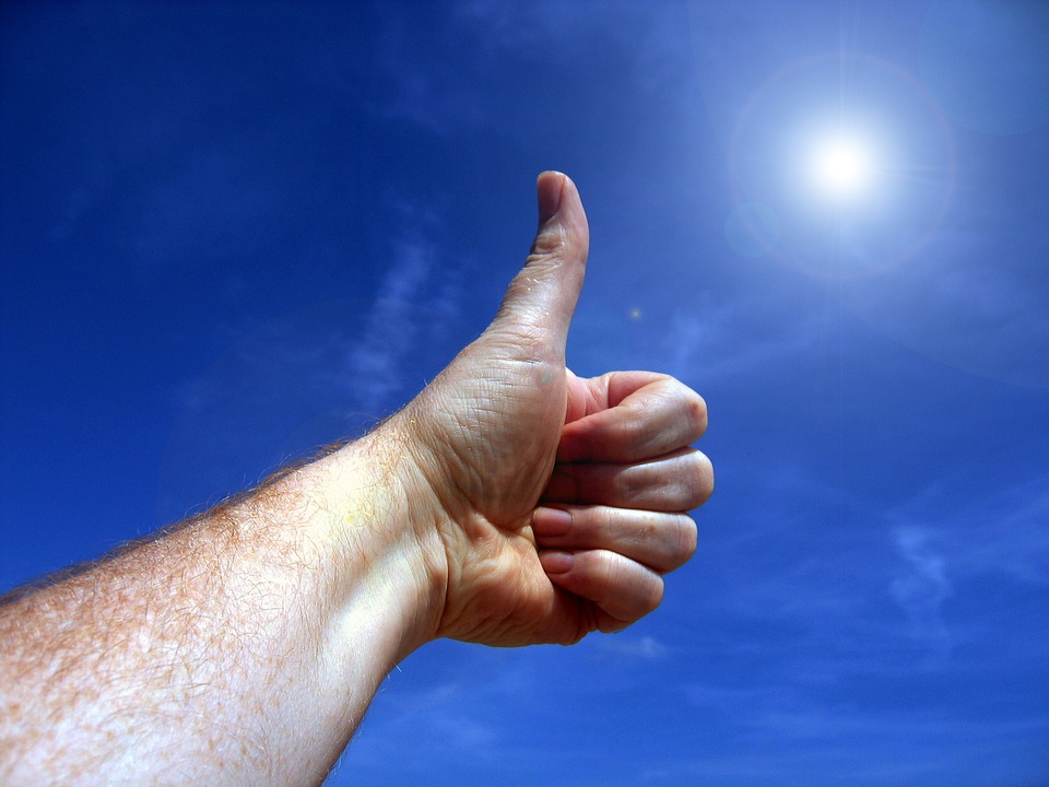 thumbs up against a blue, almost noon day sun