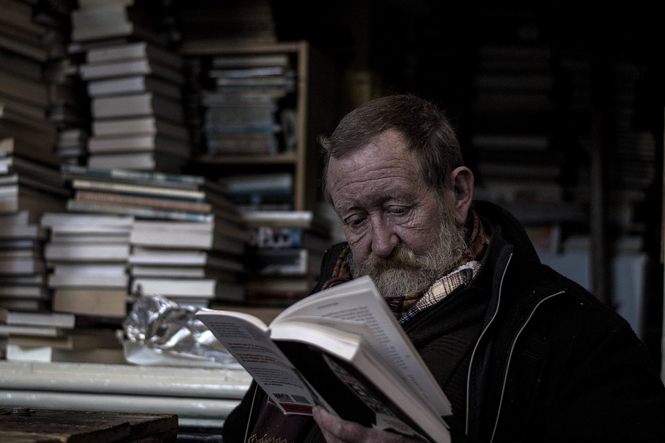 man reading a book in front of an a room full of books