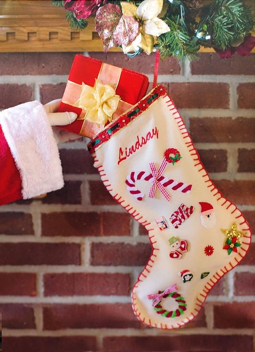 santa hand putting present in stocking