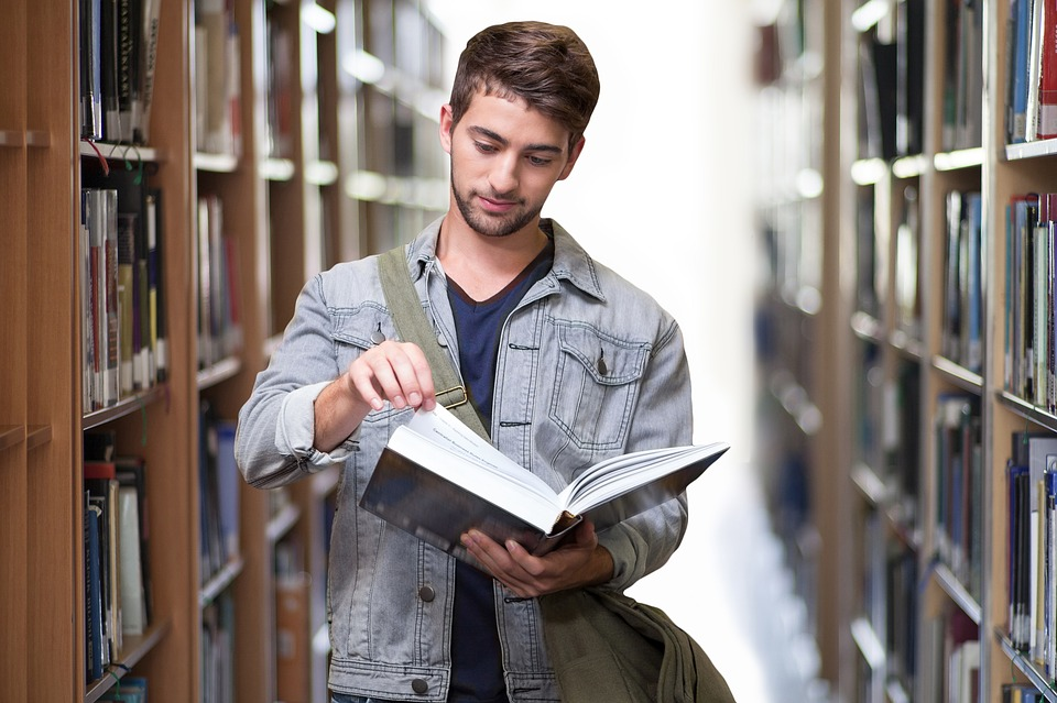 student with book looking happy with library in the background