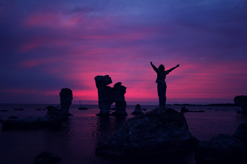 person standing on hill with arms raised in dusk