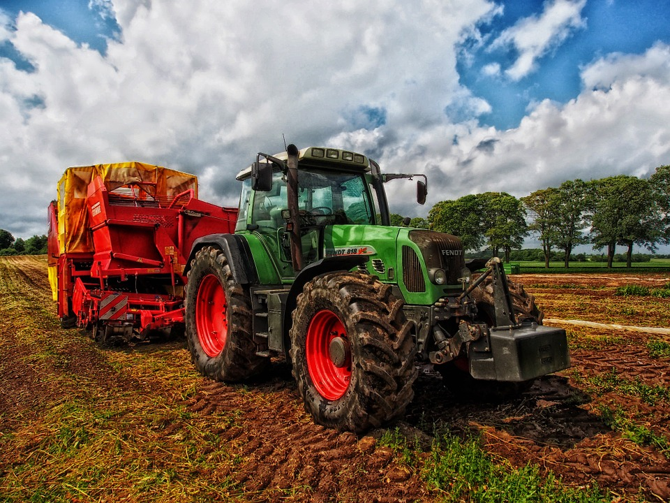 A green tractor is in the middle of a field with trees in the background