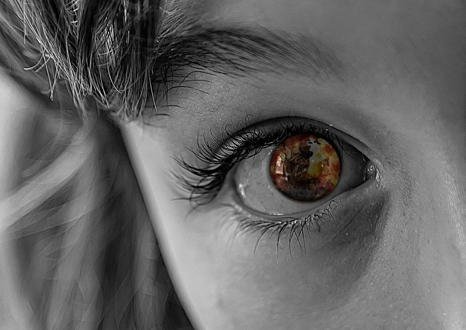 frightened child staring with an explosion reflected in their eye