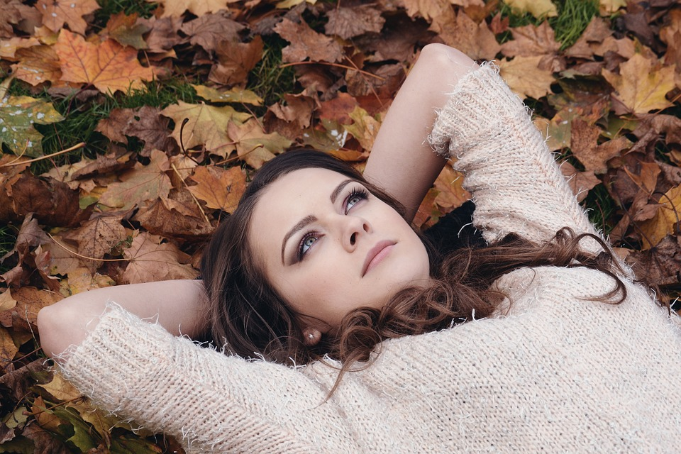 woman in deep thought over some autumn leaves