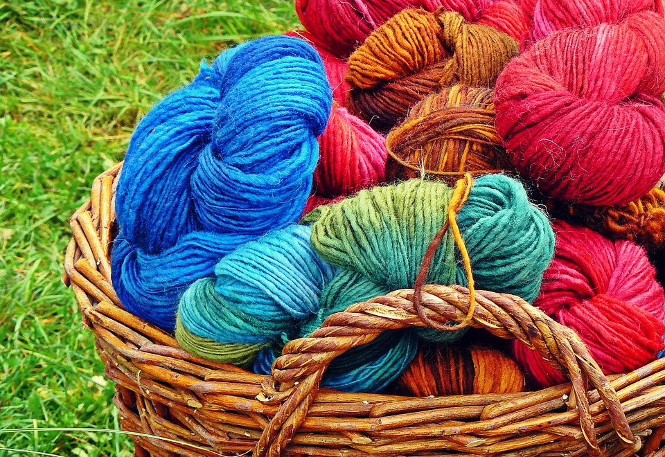 basket of different coloured wools on grass
