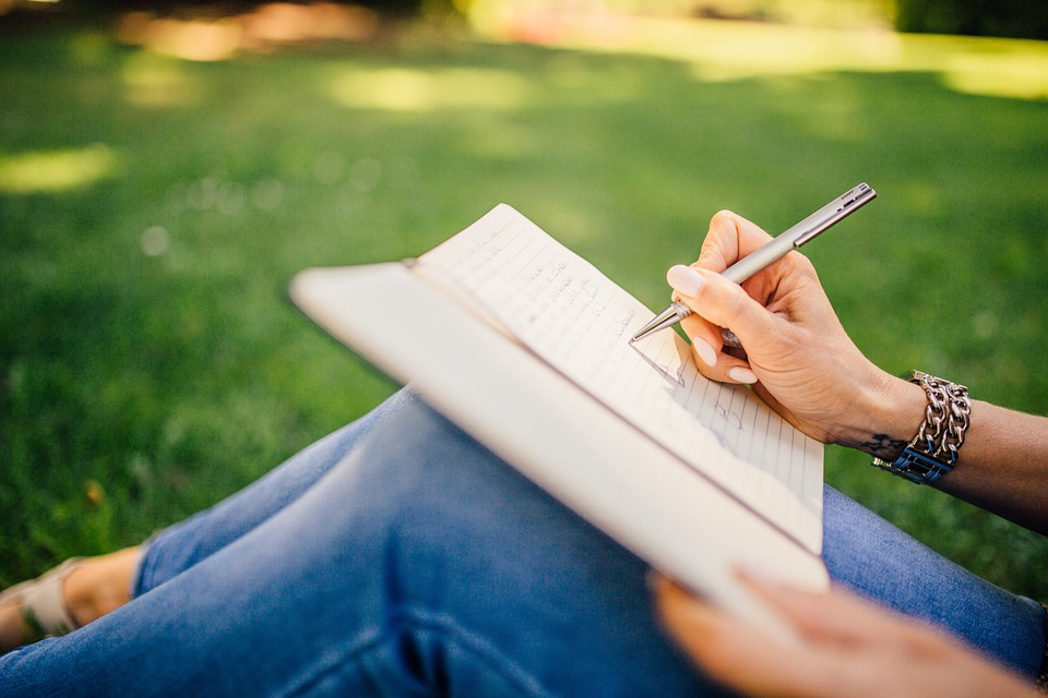 person writing against a tree on grass
