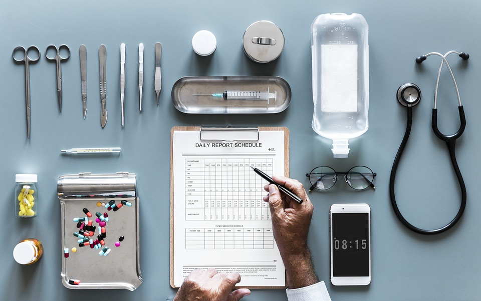 A doctor is writing a daily report schedule on a table with lots of pill and medical equipment