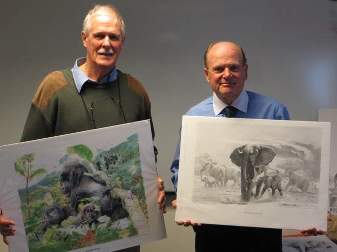 Chris McClelland holding drawings of wild animals