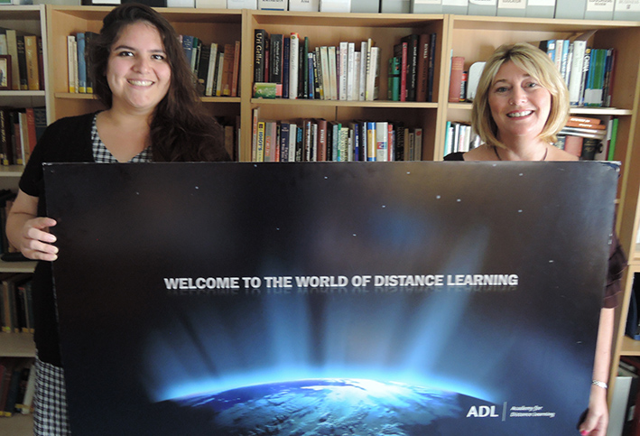 Student support team Maryanne and Amanda display a Welcome to the World of Distance Learning Banner