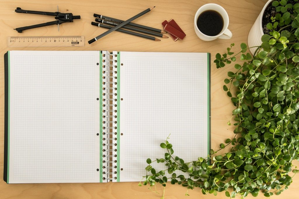 A beautifully laid out desk with pencils, a ruler, and a coffee cup surrounded by greenery