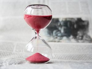 A clear hourglass pouring red sand, it looks contemplative