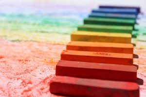 A series of colourful crayons are lined up on paper