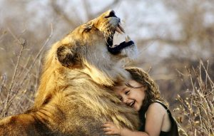 A lion hugs a young child, the story of the beauty and the best comes to mind