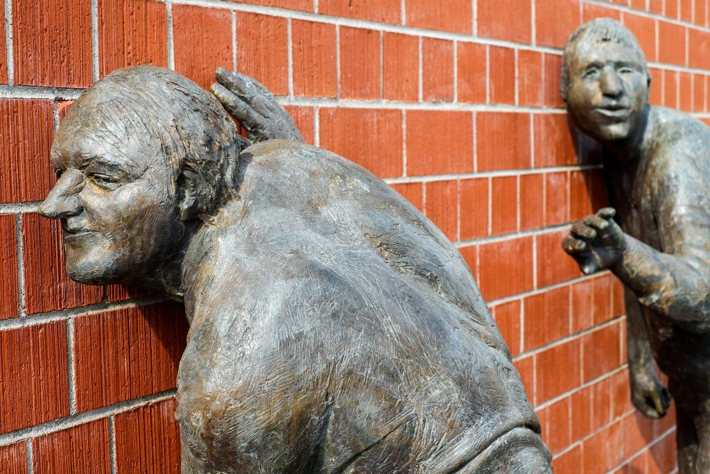 Sculptures of people put their ears to a brick wall, I wonder what they hear