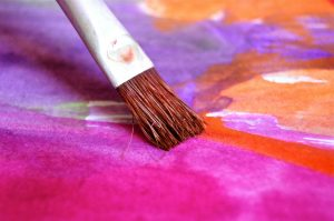 A brush touches painted piece of paper we can't see the whole picture being painted just colours and shapes