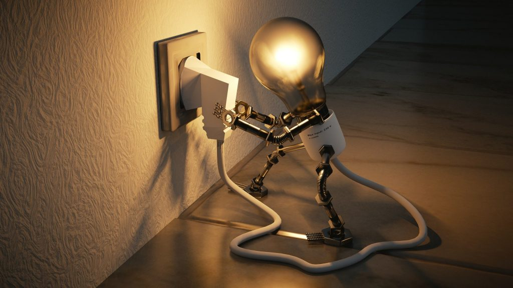 A light bulb with arms is plugging itself into the wall, perhaps it had a good idea