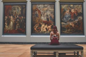 A woman sits in an art gallery looking at some baroque paintings, though they tower over her they she seems inspired