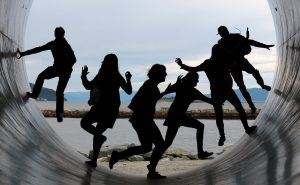 People dance inside a of a tube overlooking some plains, they look like they are having a good time.