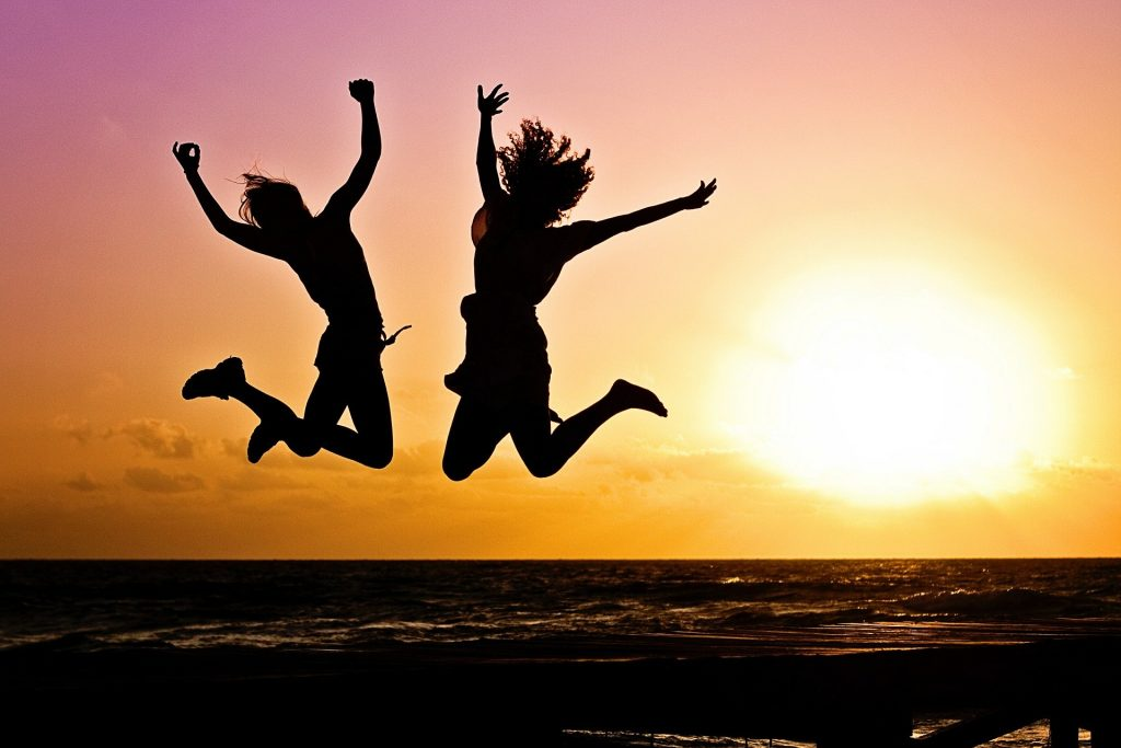Two people captured in mid air celebrating the sun shines brightly behind them