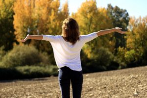 An open green space with a women with her arms outstretched, it looks idyllic