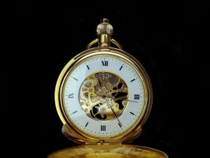 A pocket watch with it's skeleton showing, you can see all of the small parts moving around